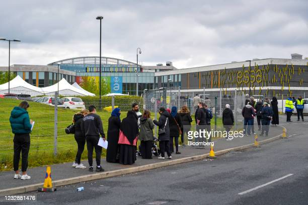 Members of the public queue to receive Covid-19 vaccinations at a pop-up vaccination bus parked at Essa Academy in the Daubhill area of Bolton, U.K.,...