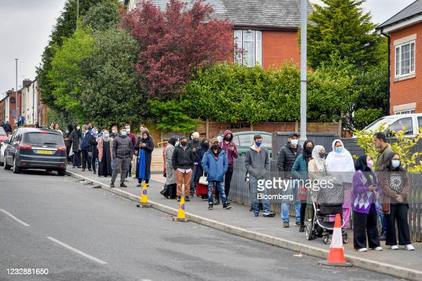 Members of the public queue to receive COVID-19 vaccinations in a pop-up vaccination bus parked at Essa Academy in the Daubhill area of Bolton, U.K.,...