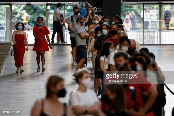 Members of the public queue to receive the Pfizer-BioNTech Covid-19 vaccine in the Turbine Hall at a temporary Covid-19 vaccine centre at the Tate...