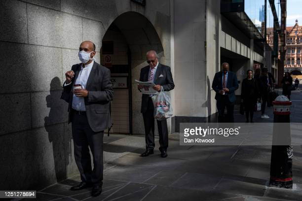 Members of the public queue while maintaining social distancing measures outside the Old Bailey courthouse on June 22, 2020 in London, England. HM...