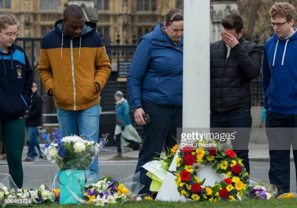 Members of the public react as they leave floral tributes in Parliament Square on the first anniversary of the Westminster Bridge terror attack on...