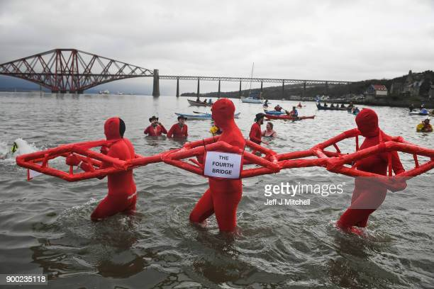 Members of the public react to the water as they join around 1100 New Year swimmers many in costume in front of the Forth Rail Bridge during the...