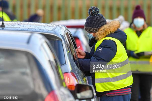 Members of the public receive vaccinations at a drive-through vaccine center in Hyde, near Manchester, U.K., on Friday, Jan. 8, 2021. U.K. Prime...