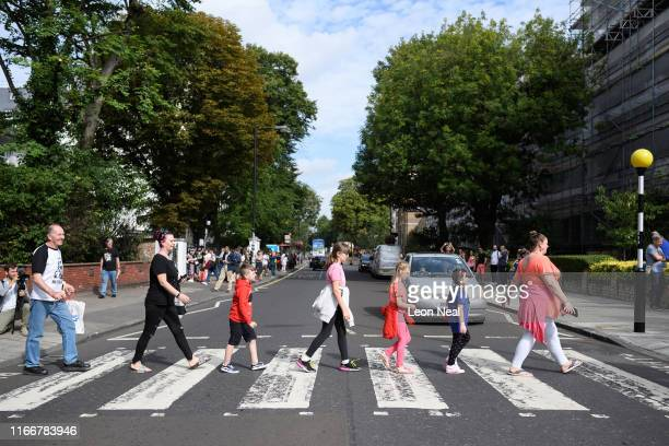 Members of the public recreate the iconic album cover for the Beatles album Abbey Road on the same pedestrian crossing fifty years since it was taken...