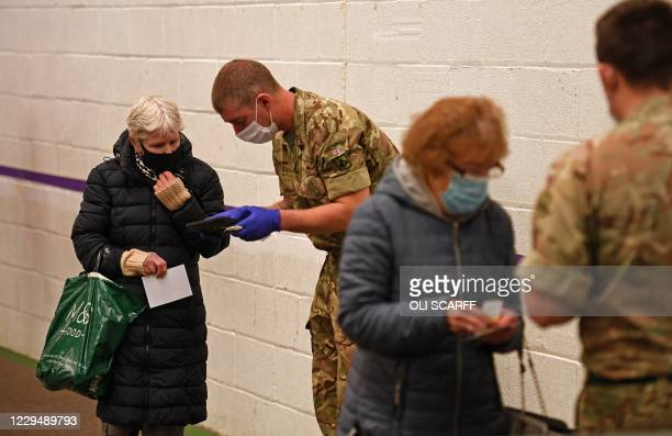 Members of the public register with soldiers as they arrive to be tested at the mass and rapid testing centre for the novel coronavirus COVID-19 at a...