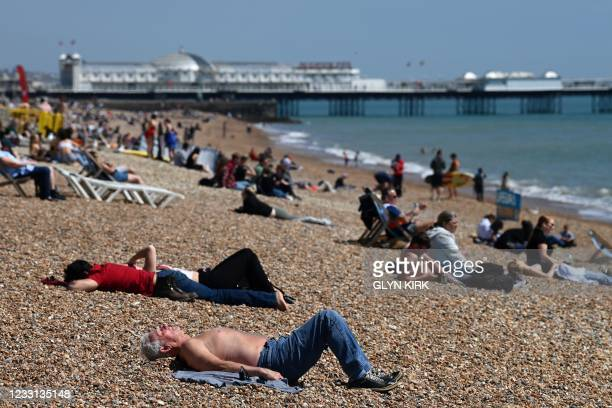 Members of the public relax on Brighton beach in Brighton, southern England as temperatures rise across the country on May 27, 2021.