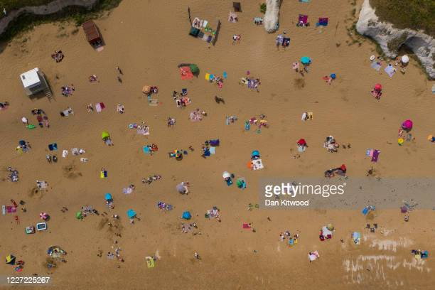 Members of the public relax on the beach at Botany Bay on May 26, 2020 in Margate, England. The British government continues to ease the coronavirus...