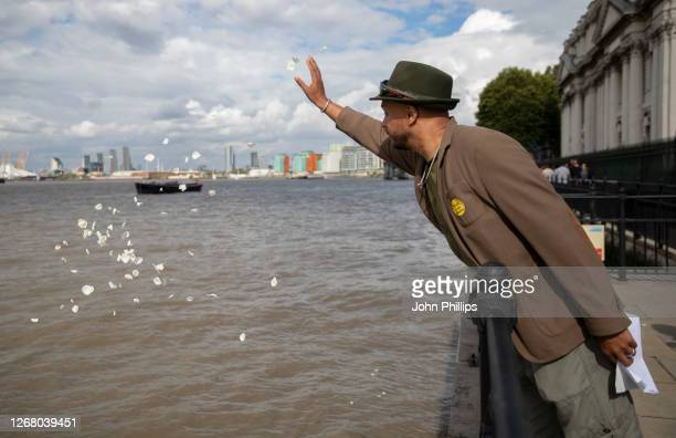 Members of the public scatter white rose petals onto the river Thames in an act of commemoration during an Emancipation Ceremony held at the National...