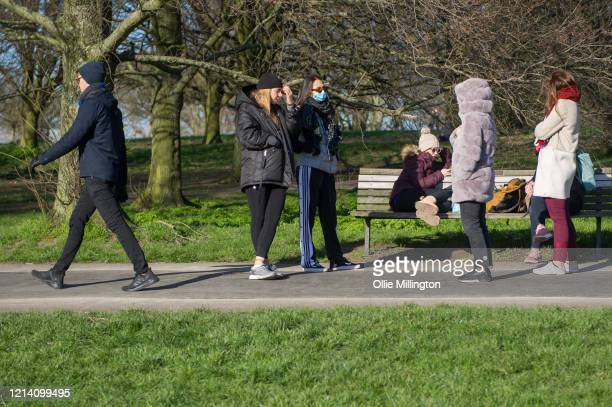 Members of the public seen congregating with friends on Primrose Hill on March 22, 2020 in London, England. Coronavirus has spread to at least 188...