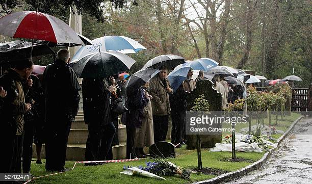 Members of the public shield themselves from the elements in the grounds of The Parish Church of Saint Mary the Virgin as the funeral of Sir John...