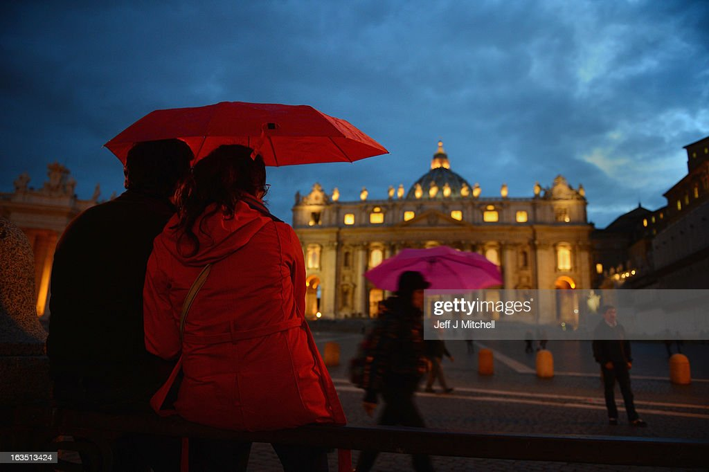 Members of the public sit in front of St Peter's Basilica on March 11, 2013 in Vatican City, Vatican. Cardinals are set to enter the conclave to elect a successor to Pope Benedict XVI after he became the first pope in 600 years to resign from the role. The conclave is scheduled to start on March 12 inside the Sistine Chapel and will be attended by 115 cardinals as they vote to select the 266th Pope of the Catholic Church.