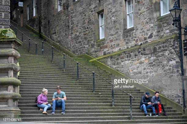 Members of the public sit on the steps in Princess Street as a new law comes into force limiting social gatherings to a maximum of six people from...