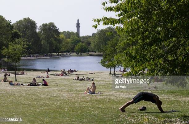 Members of the public sitting and exercising in Regent's Park by the lake on a sunny warm afternoon on May 09 2020 in London United Kingdom The...