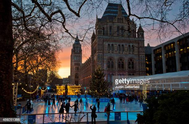 Members of the public skate as the sun sets on Christmas eve at the ice rink infront of the Natural History Museum on December 24 2013 in London...
