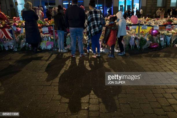 Members of the public stand before floral tributes following a vigil on St Ann's Square in Manchester northwest England on May 29 exactly one week...