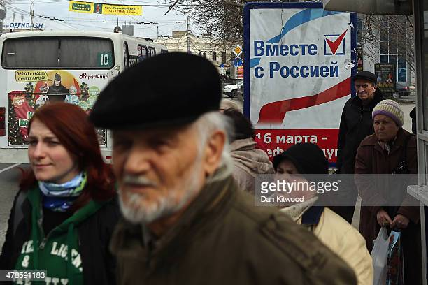 Members of the public stand by a sign that reads 'Together with Russia' in Russian at a bus stop on March 14 2014 in Simferopol Ukraine As the...
