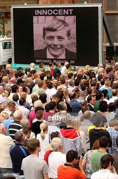Members of the public stand in front of a giant screen proclaiming the innocence of those killed in the Bloody Sunday shootings outside the Guildhall...