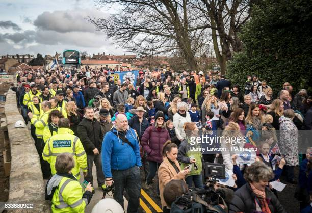 Members of the public stand on Tadcaster Bridge as it reopens more than a year after its partial collapse which came to symbolise the destruction of...