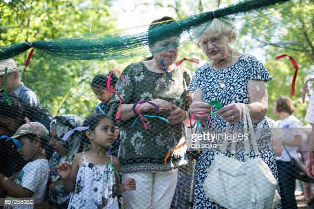 Members of the public symbolically tie ribbons onto a piece of netting during a 'Great Get Together' community service and picnic in memory of Jo Cox...