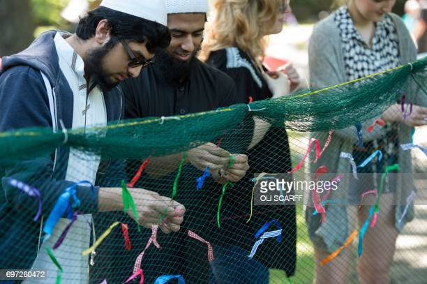 Members of the public symbolically tie ribbons onto a piece of netting during a 'Great Get Together' community service and picnic in memory of...