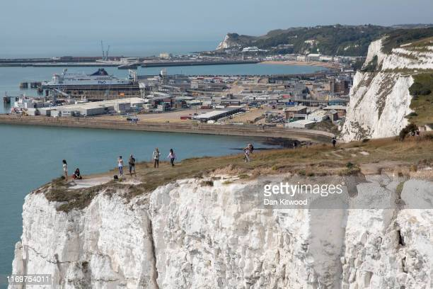 Members of the public take photographs from the top of the white cliffs overlooking Dover Port on August 23, 2019 in Dover, England. Traffic is...