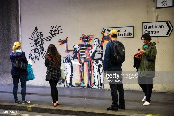 Members of the public take photographs of a new work by street artist Banksy on a wall by the Barbican Centre on September 18 2017 in London England...