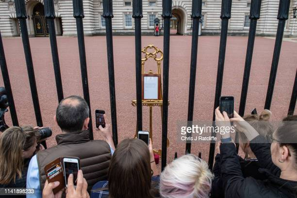 Members of the public take photographs of the official notice of the birth of a baby boy to the Duke and Duchess of Sussex outside Buckingham Palace...