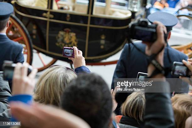 Members of the public take photographs of the Queen's carriage during the Royal Wedding of Prince William to Catherine Middleton at Westminster Abbey...
