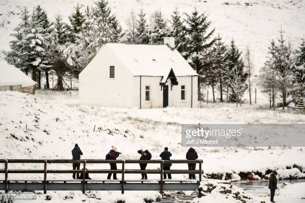 Members of the public take pictures of Lagangarbh cottage below Buachaille Etive Mor on February 1, 2019 in Glen Coe Scotland. The Met office have...