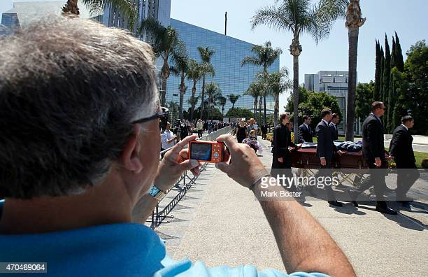 """Members of the public take pictures while pallbearers roll the coffin of """"Hour Of Power"""" and Crystal Cathedral founder, Robert H. Schuller past them..."""