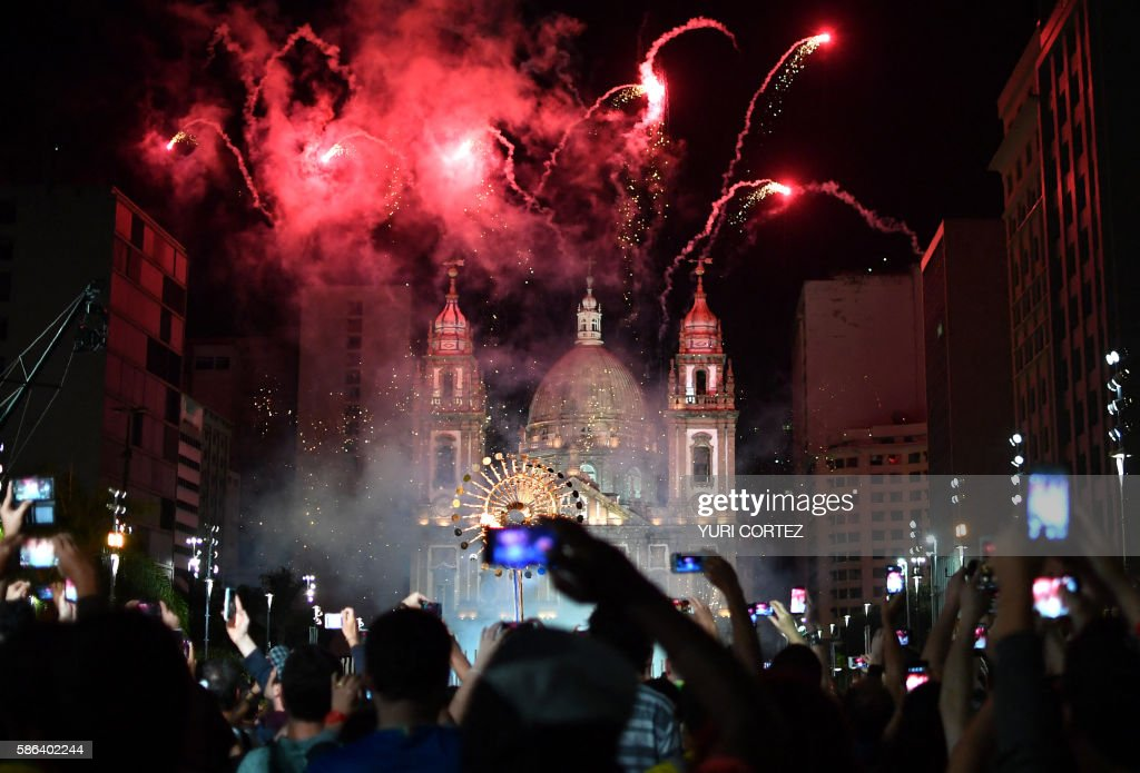 TOPSHOT - Members of the public take smartphone pictures as the Olympic Cauldron at the Candelaria Church in downtown Rio de Janeiro at the end of the opening ceremony of the Rio 2016 Olympic Games on August 5, 2016. / AFP / Yuri CORTEZ
