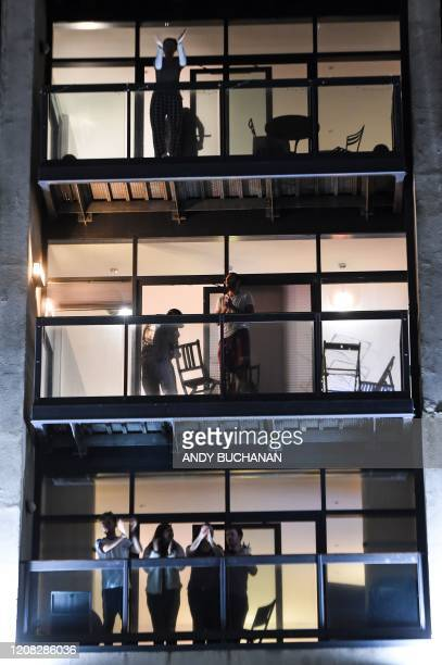 Members of the public take to balconies for a period of applause in Glasgow Scotland on March 26 as a sign of public admiration for the National...