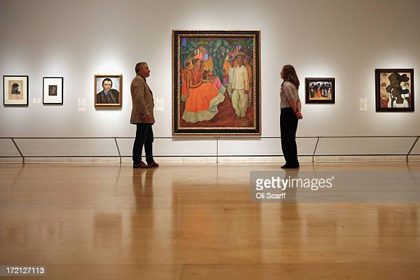 Members of the public view a painting by Diego Rivera entitled 'Dance in Tehuantepec' in the Royal Academy of Arts on July 2 2013 in London England...