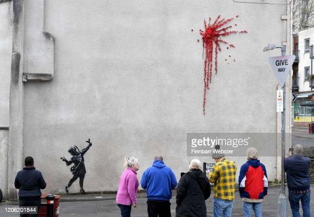 Members of the public view the new Banksy art on February 14 2020 in Bristol England The artwork of a girl firing flowers into the air appeared on...