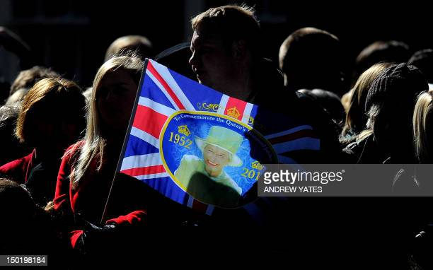 Members of the public wait for Britain's Queen Elizabeth II holding a flag commemorating the queen's diamond jubilee at the Royal Maundy Service at...