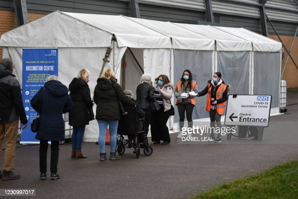 Members of the public wait in a queue to receive a dose of a Covid-19 vaccine at a temporary coronavirus vaccination hub set up at the Colchester...