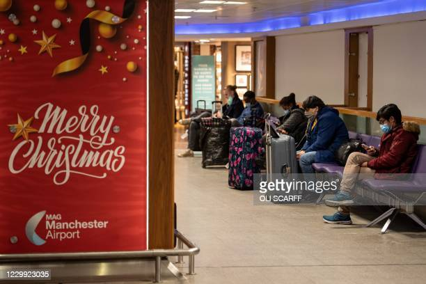 Members of the public wait next to a poster wishing passengers a merry Christmas, at Terminal 1 of Manchester Airport in Manchester, northern England...