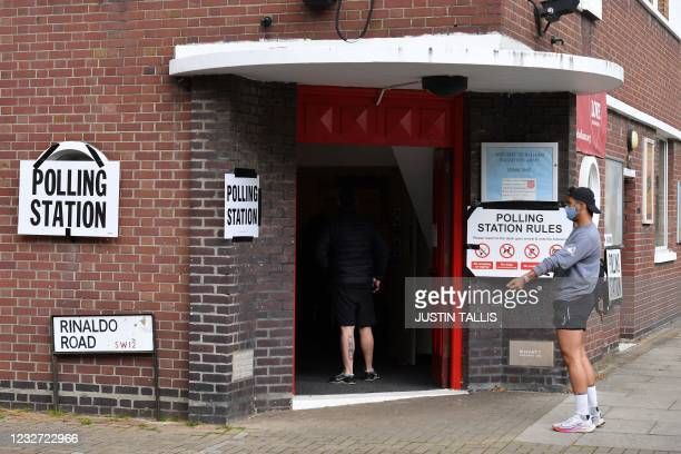 Members of the public wait to cast votes at a polling station in southwest London as the country votes in local elections on May 6, 2021. - Britain...