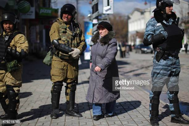 Members of the public walk between a line of Russian and Ukrainian Berkut riot police on March 17 2014 in Simferopol Ukraine Voters on the autonomous...