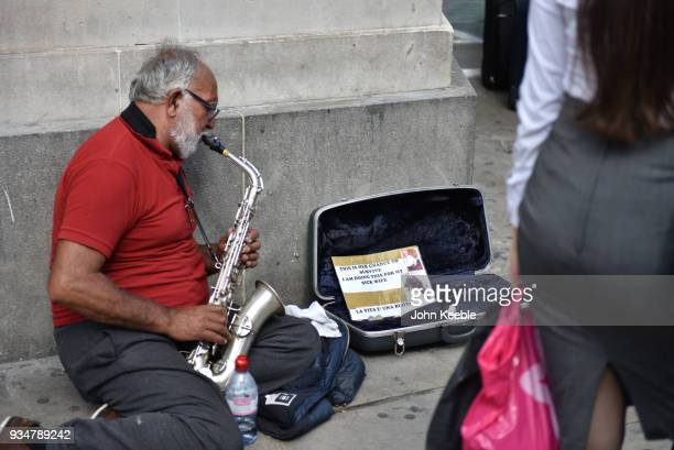 Members of the public walk by as a man plays a saxophone for money to help his sick wife outside Bank tube station close to the Bank of England on...