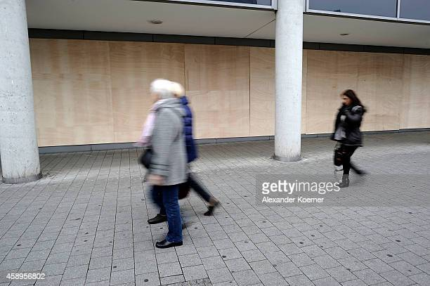 Members of the public walk by the covered glass facade of the Novotel Hotel at Hanover Central Trainstation on November 14 2014 in Hanover Germany...