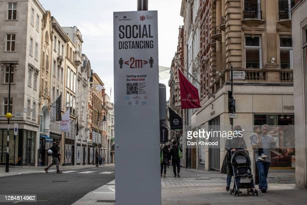Members of the public walk down an quiet New Bond Street on November 09, 2020 in London, England. Retailers hope the current lockdown measures, which...