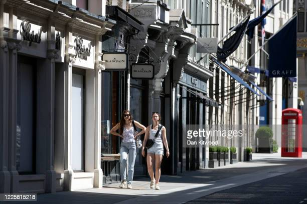 Members of the public walk down New Bond Street on May 19 2020 in London England As shops gear up to open after a long period of closure clothing...