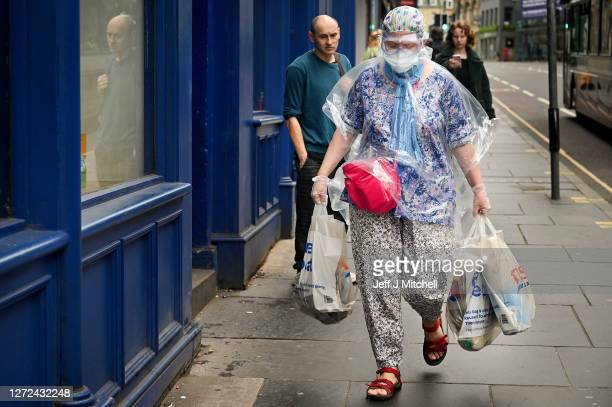Members of the public walk down Princess Street as a new law comes into force limiting social gatherings to a maximum of six people from two...