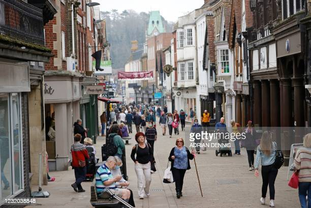 Members of the public walk down the High Street in Winchester, south west England on March 31, 2021.