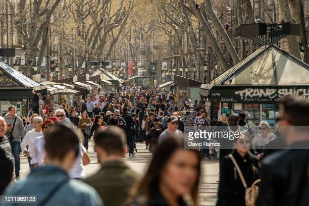 Members of the public walk down the tourist spot of Las Ramblas street on March 12, 2020 in Barcelona, Spain. The number of people confirmed to be...