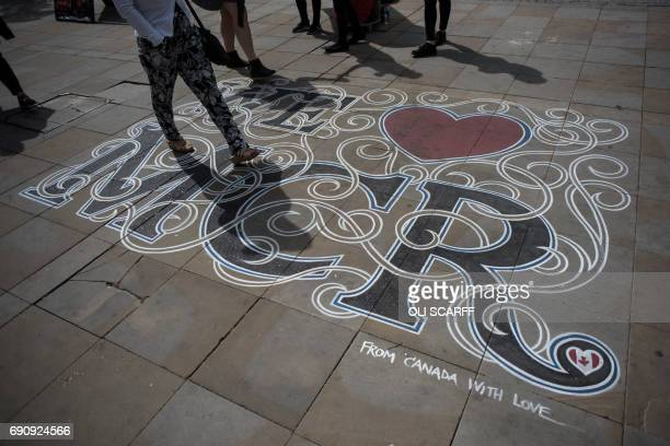 Members of the public walk over a pavement artwork displaying a message of defiance to the terror attack of May 22 at the Manchester Arena in...