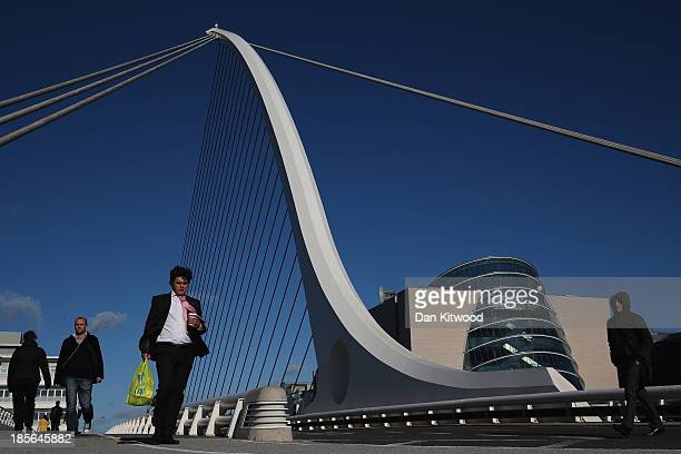 Members of the public walk over the Samuel Beckett Bridge on October 23 2013 in Dublin Ireland The bridge was designed by Santiago Calatrava and...
