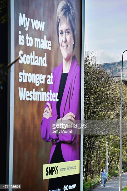 Members of the public walk past a billboard of First Minister of Scotland and leader of the SNP Nicola Sturgeon on the A82 on April 28 2015 in...