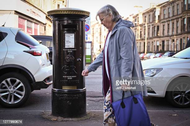 Members of the public walk past a black postbox on Byres Road featuring an image of Second Lieutenant Walter Tull it is one of four special edition...